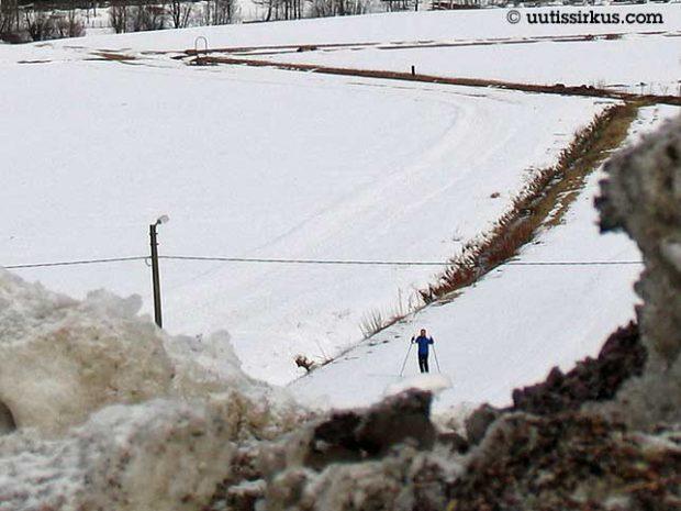 Snön är smutsig men en man skider därborta