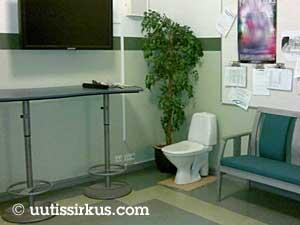 Aulassa on televisio, ruukkukasvi ja wc-pönttö