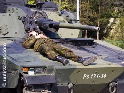 Varusmies nukkuu panssariajoneuvon konepellillä