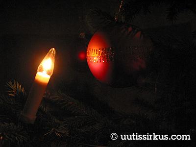 joulukuusessa sähkkynttilä ja punainen lasipallo