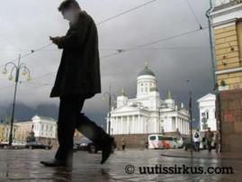 Mies kävelee Senaatintorin laita katse kiinteästi puhelimessaan