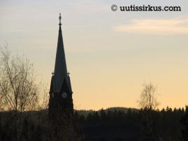 kirkontorni ulottuu horisontin yläpuolelle kuulaassa syysilmassa