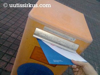 Kirje sujahtaa kädestä postin laatikkoon
