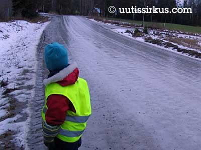 heijastinliivit päällä seisoo poika täysin jäätyneen tien laidassa
