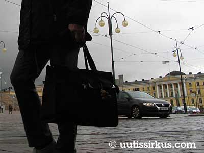 Senaatintori, valtioneuvoston linna ja isoa kassia kantava ihminen.