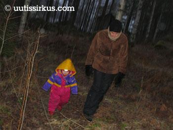 äiti kulkee lapsen kanssa synkeässä metsässä