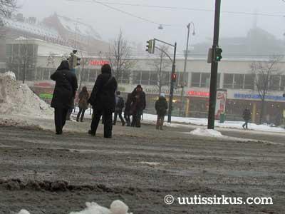 ihmiset laahustavat sohjoisen kadun yli Helsingin Lasipalatsin liepeillä