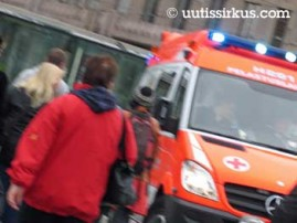 työntekijä kulkee pihalla ja ambulanssi kaartaa ohi