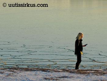 nainen kulkee jäisen meren rantaa ja tuijottelee puhelintaan