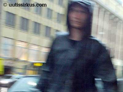 mies rientää sadetakki yllään kadulla