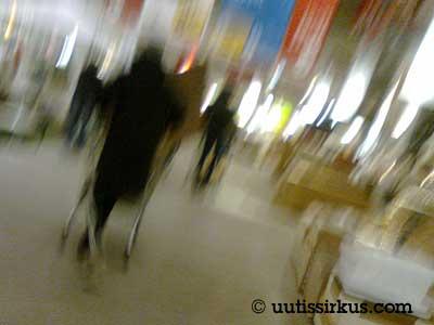 Ikean varastohallissa ihmiset työntelevät kärryjä