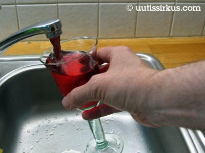 vesihanasta valuu punaista nestettä viinilasiin