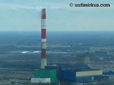 puna-valkoinen tehtaanpiippu ja siinen teollisuushalli