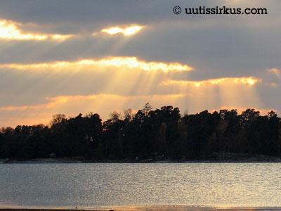 auringonsäteet pilkistävät pilvien alta ja osuvat metsään ja mereen