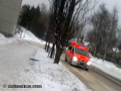 ambulanssi ajaa sohjoisella väylällä aavistuksenomaisesti tärähtäneessä valokuvassa