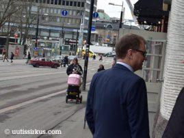 nainen työntää lastenvaunuja kadulla ja Juha Sipilä on menemäisillään kahvilan ovesta sisälle