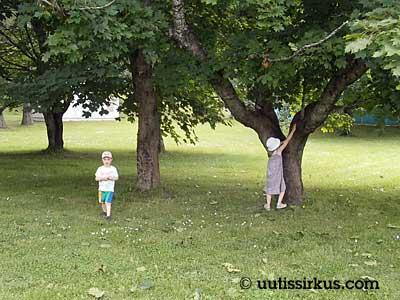 lapset puun alla, tyttö kiipeämäisillään puuhun, poika kävelee poispäin