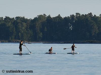 kolme henkilöä suppaa rannalla