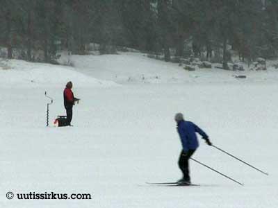 jäällä mies pilkkii ja toinen hiihtää