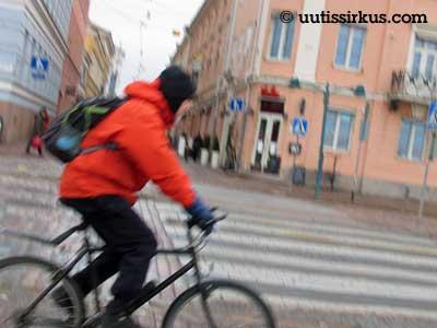 pyöräilijä polkee oranssi takki yllään