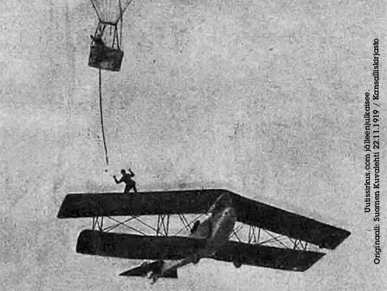 Harry Hill tasapainoilee lentokoneen siivellä ja kurottelee kohti kuumailmapallosta roikkuvaa köyttä