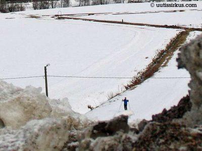 hiihtäjä hiihtää pellolla, etualalla likaisia lumikökkäreitä