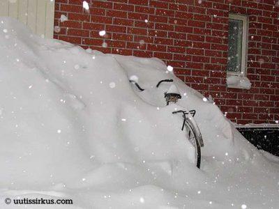 polkupyörä talon seinän vieressä umpihangessa
