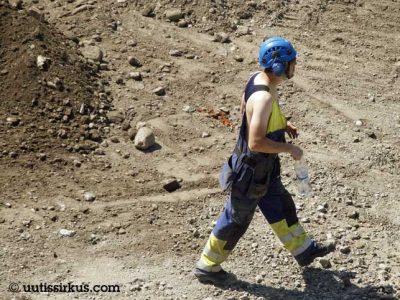 rakennusmies kävelee sorakentällä sininen kypärä päässään, yllä haalarit, ei paitaa, on siis kesä