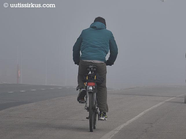 mies pyöräilee sumuisella Lauttasaaren sillalla