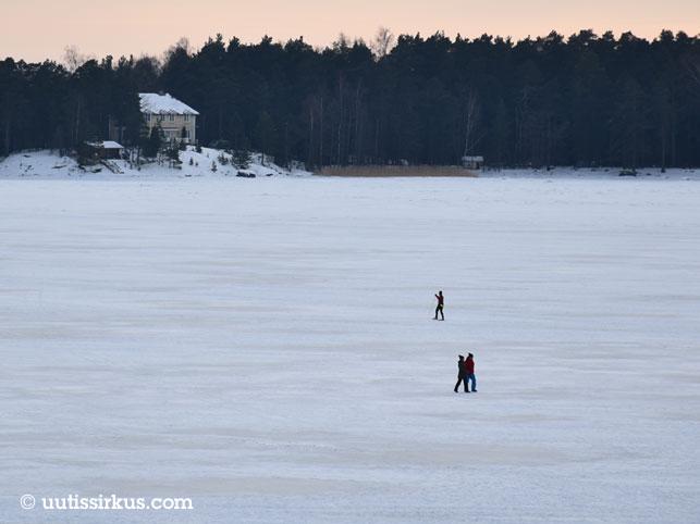 autio merenlahti, jonka jäällä näkyy yksi hiihtäjä ja kaksi kävelijää
