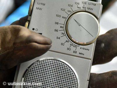työhanskaan verhottu käsi pitelee pientä matkaradiota