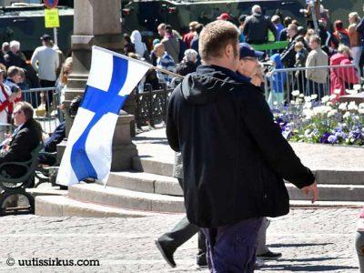 mies kulkee torilla Suomen lippu olallaan, takana väkijoukkoa