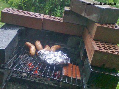 neljä makkaraa grillissä ritilällä hehuvien hiilien päällä
