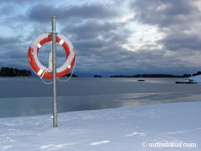 meren rannassa lunta, pelastusrengas ja tammikuisena pilvien takaa haaleana hohtava aurinko