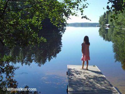 tyttö seisoo laiturilla ja katselee tyyneen veteen auringon paisteessa