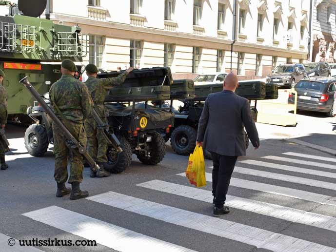 Pukumies kulkee sotilaiden ohi Alepa-kassi kädessään