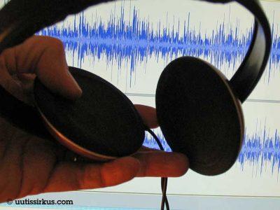 kädessä kuulokkeet, joiden takana näkyy näytöltä äänikäyrää