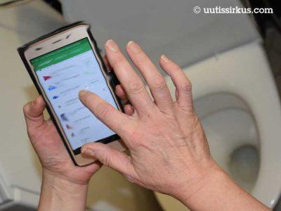 kännykkä kädessä, sen alapuolella vessanpönttö