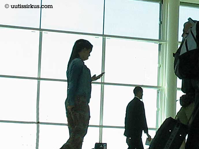 nainen kävelee, tuijottaa kännykkäänsä