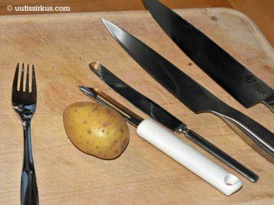 leikkuulaudalla perunan vieressä neljä erilaista veistä ja yksi haarukka