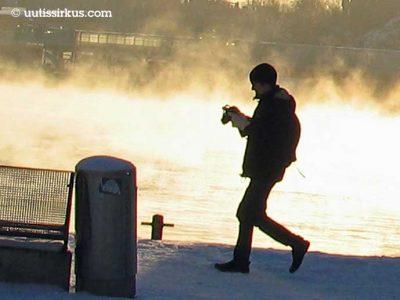 mies kävelee talvisella laiturilla, takana höyryävää vettä