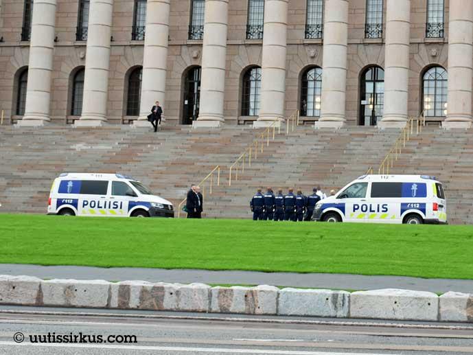 kaksi poliisiautoa ja poliiseja eduskuntatalon portaiden edustalla