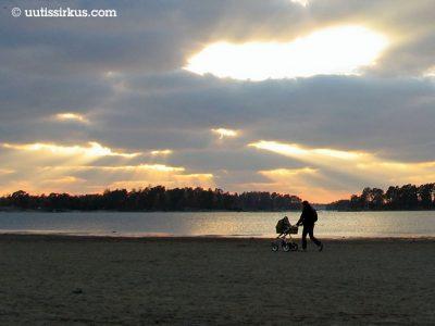 mies työntää lastenvaunuja rannassa, auringonsäteet osuvat pilvien lomasta vesistön takana häämöttävään saareen