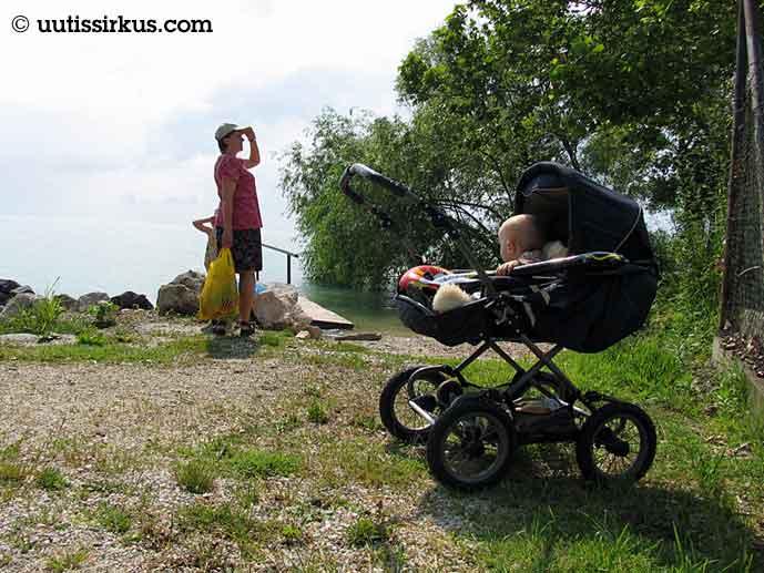 äiti tähyilee ilmeisesti puuhun kiivennyttä lastaan, etualalla vaunuissa toinen lapsi
