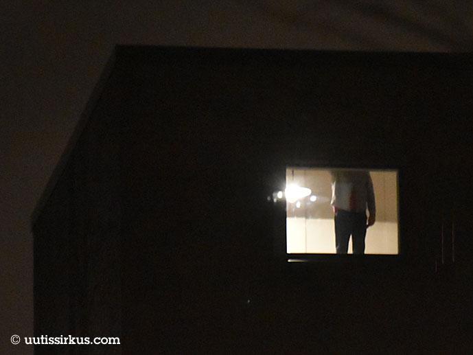 miehen keho näkyy kerrostalon ikkunasta, pää ja osa jaloista jäävät ikkunankehyksen taakse