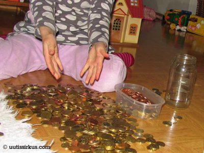lapsi, edessään lattialla runsaasti kolikoita