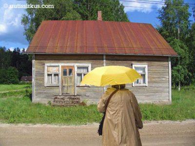 sateenvarjoa pitelevä nainen ränsistyneen hirsitalon edessä auringonpaisteessa