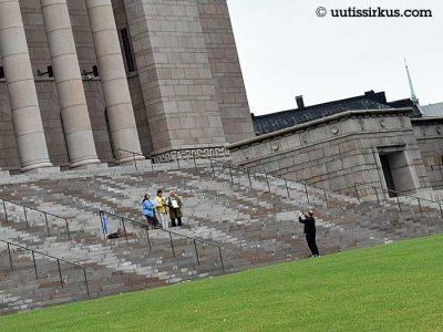 kolme ihmistä seisoo eduskuntatalon portailla, neljäs ottaa heistä valokuvaa