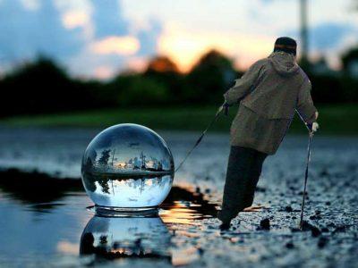 sauvakävelijä kulkee rannaal vinossa veden rajassa olevan kristallipallon vieressä