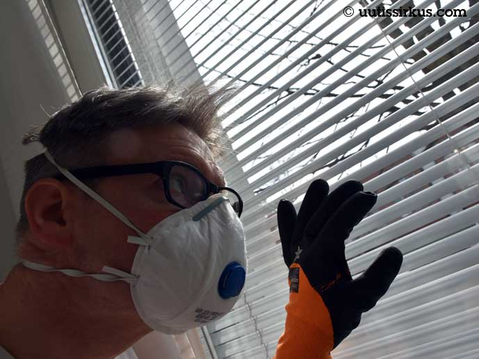 Hengityssuojaimella ja kumikäsineillä varustautunut mies tähyilee sälekaihtimen välistä
